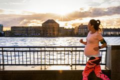 Pregnant woman running outside in a city at the riverside royalty free stock images