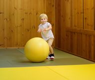 Active preschool boy playing with big ball in indoor sports hall/gym class. Active preschool boy playing with big ball in indoor sports hall. Kids active game royalty free stock photography