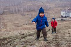 Active preschool children climb the path to the high mountain in spring, spring landscape. Nature sleeps stock photo