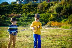 Active preschool girl and boy playing badminton in outdoor court in summer. Kids play tennis. School sports for children. Racquet. Two active preschool boy royalty free stock images