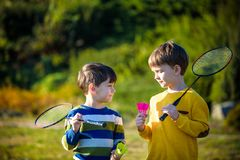 Active preschool girl and boy playing badminton in outdoor court in summer. Kids play tennis. School sports for children. Racquet. Two active preschool boy stock image