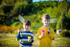 Active preschool girl and boy playing badminton in outdoor court in summer. Kids play tennis. School sports for children. Racquet. Two active preschool boy stock photo