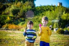 Active preschool girl and boy playing badminton in outdoor court in summer. Kids play tennis. School sports for children. Racquet. Two active preschool boy royalty free stock photo