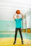 Active preteen girl tossing basketball in rim Stock Photos