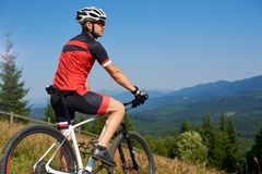 Active professional sportsman cyclist stopped bicycle on top of hill. To enjoy beautiful view of distant Carpathian mountains on blue summer sky background stock photography