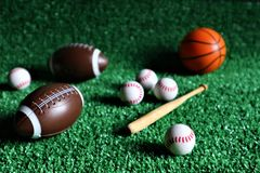 Collection of several sport game balls such as football, soccer, and tennis, flying on a green background royalty free stock photography
