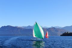 Active rest on clear sunny day. Yachts with red and green sail on lake surrounded by mountains. stock photo