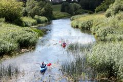 Active rest on the river. People on kayaks are sailing along a plain small river. Stock Photos