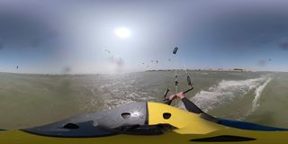 360 degrees, a man in a helmet with a camera is riding the sea, people are kitesurfing stock video footage