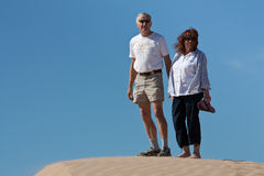 Active retired couple at the dunes. An active senior couple stands at the top of a breezy sand dune, looking relaxed and happy Lots of blue sky for copy space Stock Images