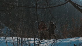 Active retired couple walking in the snow stock video footage