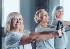 Excited senior lady holding weight disk while training stock images