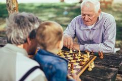 Senior men having fun and playing chess at park. Active retired people, old friends and free time, two senior men having fun and playing chess at park, spend stock images
