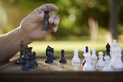 Active retired people, senior man playing chess at park. Active retired persons, hand of old man holding chess piece in park. Closeup shot, copy space stock image