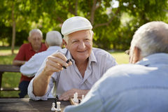 Active retired seniors, two old men playing chess at park royalty free stock photography