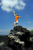 Active Retirement. Woman celebrates her retirement standing on top of her mountain.  She has climbed to the top of a black lava rock on the Big Island of Hawaii Royalty Free Stock Photography