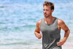 Active runner sweating running on summer beach royalty free stock image