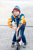 Active school kid boy in colorful casual clothes riding with his scooter in the city. Happy child in colorful clothes biking on way to school. or nursery Royalty Free Stock Image