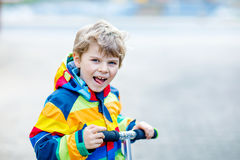 Active school kid boy in colorful casual clothes riding with his scooter in the city. Happy child in colorful clothes biking on way to school. or nursery Royalty Free Stock Photography