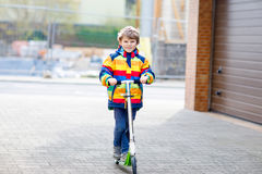 Active school kid boy in colorful casual clothes riding with his scooter in the city. Happy child in colorful clothes biking on way to school. or nursery Royalty Free Stock Photo