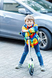 Active school kid boy in colorful casual clothes riding with his scooter in the city. Happy child in colorful clothes biking on way to school. or nursery Stock Photography