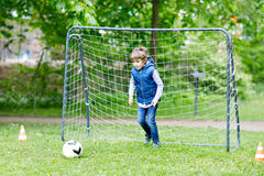 Active school kid boy playing soccer and kicking ball. Child having fun with football. Active leisure and sports for children and schoolkids Royalty Free Stock Photo