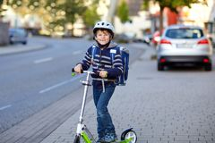 Active school kid boy in safety helmet riding with his scooter in the city with backpack on sunny day. Happy child in stock photography