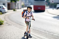 Active school kid boy in safety helmet riding with his scooter in the city with backpack on sunny day. Happy child in. Colorful clothes biking on way to school Stock Photo