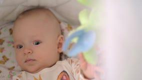 Active seis meses de bebê que joga com os brinquedos na ucha video estoque