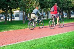 Active senior age and urban life - a couple of city dwellers a man and a woman at an age go on bicycles on the bike path. royalty free stock image
