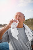 Active senior asian. An active senior asian man drinking water after exercise stock images