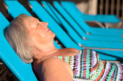 Active senior blond woman sunbathing. On a recliner chair with closed Eyes Royalty Free Stock Photos