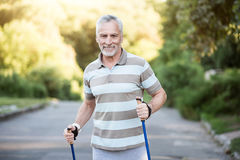 Active senior citizen jogging in the park with tracksticks Royalty Free Stock Images