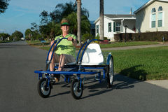 Active Senior Citizen Retirement Community. An active senior citizen woman is riding her bike in a Florida retirement community. The elderly lady is enjoying her royalty free stock photo