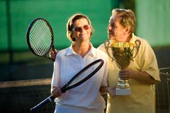 Active senior couple. Is posing on the tennis court with tennis racket and cup in hand. Outdoor, sunlight Royalty Free Stock Photo