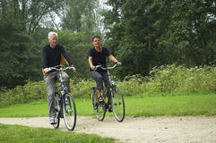 Active Senior Couple. Biking in the park Royalty Free Stock Photography