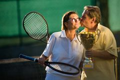 Active senior couple. Is posing on the tennis court with tennis racket and cup in hand. Outdoor, sunlight Royalty Free Stock Photography