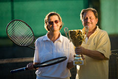 Active senior couple. Is posing on the tennis court with tennis racket and cup in hand. Outdoor, sunlight Stock Photos
