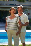 Active senior couple. Portrait of happy active senior couple posing outdoor in front of home Stock Image
