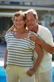 Active senior couple. Portrait of happy active senior couple posing outdoor in front of home royalty free stock image