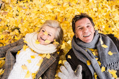 Active senior couple in autumn park lying on the ground. Covered with yellow leaves stock photo