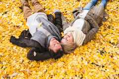 Active senior couple in autumn park lying on the ground. Covered with yellow leaves Stock Photos