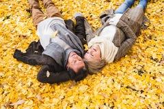 Active senior couple in autumn park lying on the ground Stock Photos