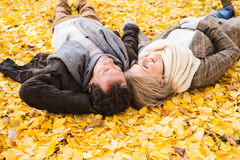 Active senior couple in autumn park lying on the ground Royalty Free Stock Photos