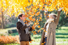 Active senior couple in autumn park throwing leaves. Active senior couple on a walk in autumn park throwing leaves Royalty Free Stock Photography