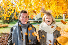 Active senior couple in autumn park throwing leaves. Active senior couple on a walk in autumn park throwing leaves Stock Image