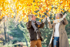 Active senior couple in autumn park throwing leaves. Active senior couple on a walk in autumn park throwing leaves Stock Photos