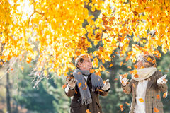 Active senior couple in autumn park throwing leaves. Active senior couple on a walk in autumn park throwing leaves Royalty Free Stock Images