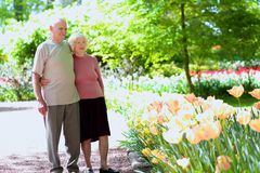 Active senior couple in beautiful flowers park Stock Images