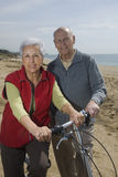 Active senior couple biking. By the sea Royalty Free Stock Images